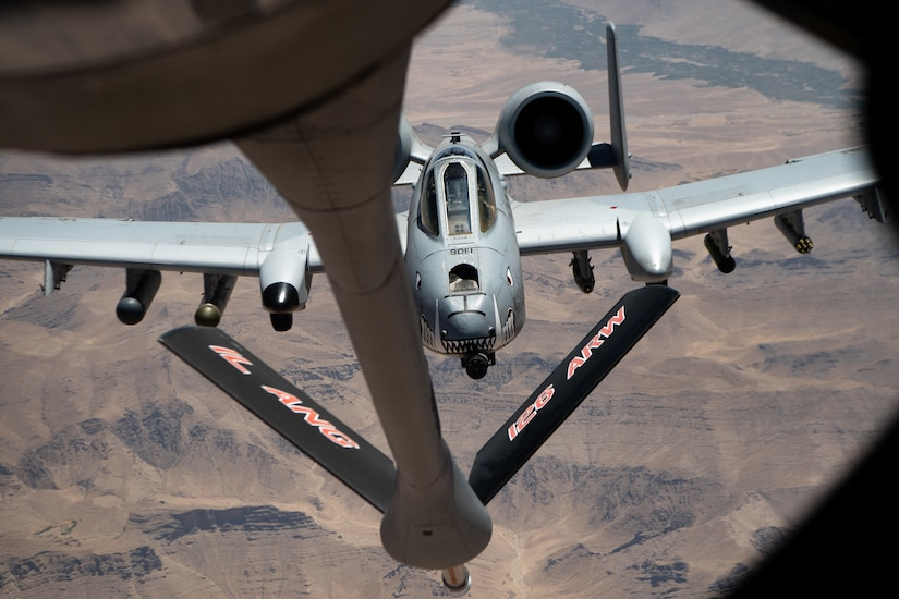 One aircraft approaches the refueling boom of another, high over desert terrain.