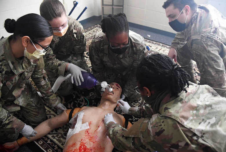 Dragon medics participate in the Tactical Combat Casualty Care training program inside the Locker House at Keesler Air Force Base, Mississippi, March 30, 2021. The training offers hands-on training in a simulated deployed environment using evidence based, life saving techniques and strategies to provide the best trauma care possible on the battlefield. (U.S. Air Force photo by Kemberly Groue)
