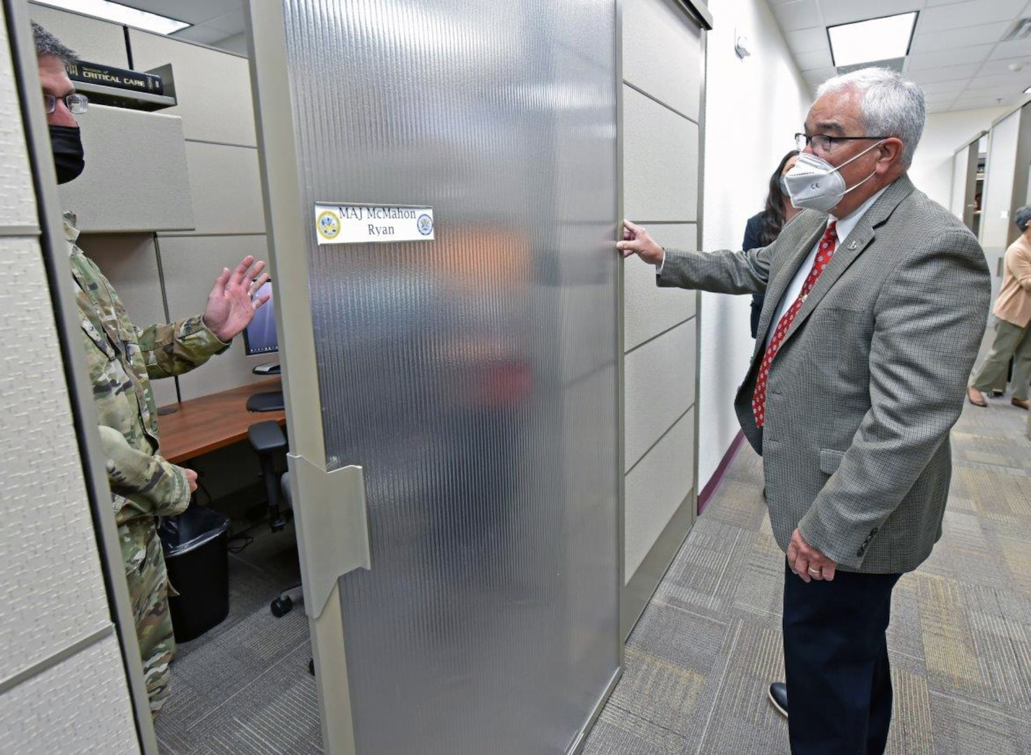 Maj. Ryan McMahon, professor of surgery and Director of Basic Life Support, demonstrates the sliding door of his new office partition to J.M. Harmon III, Deputy to the U.S. Army Medical Center of Excellence commanding general.