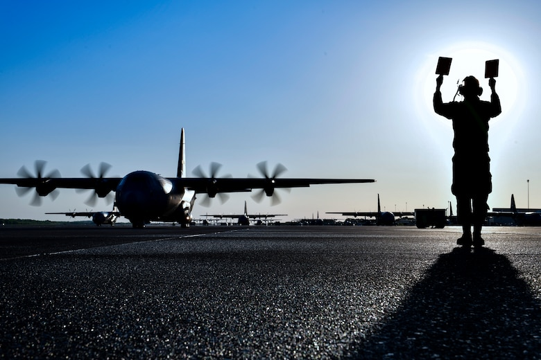 A crew chief marshals out a C-130J