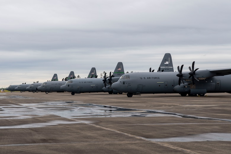 C-130Js are parked on the flightline