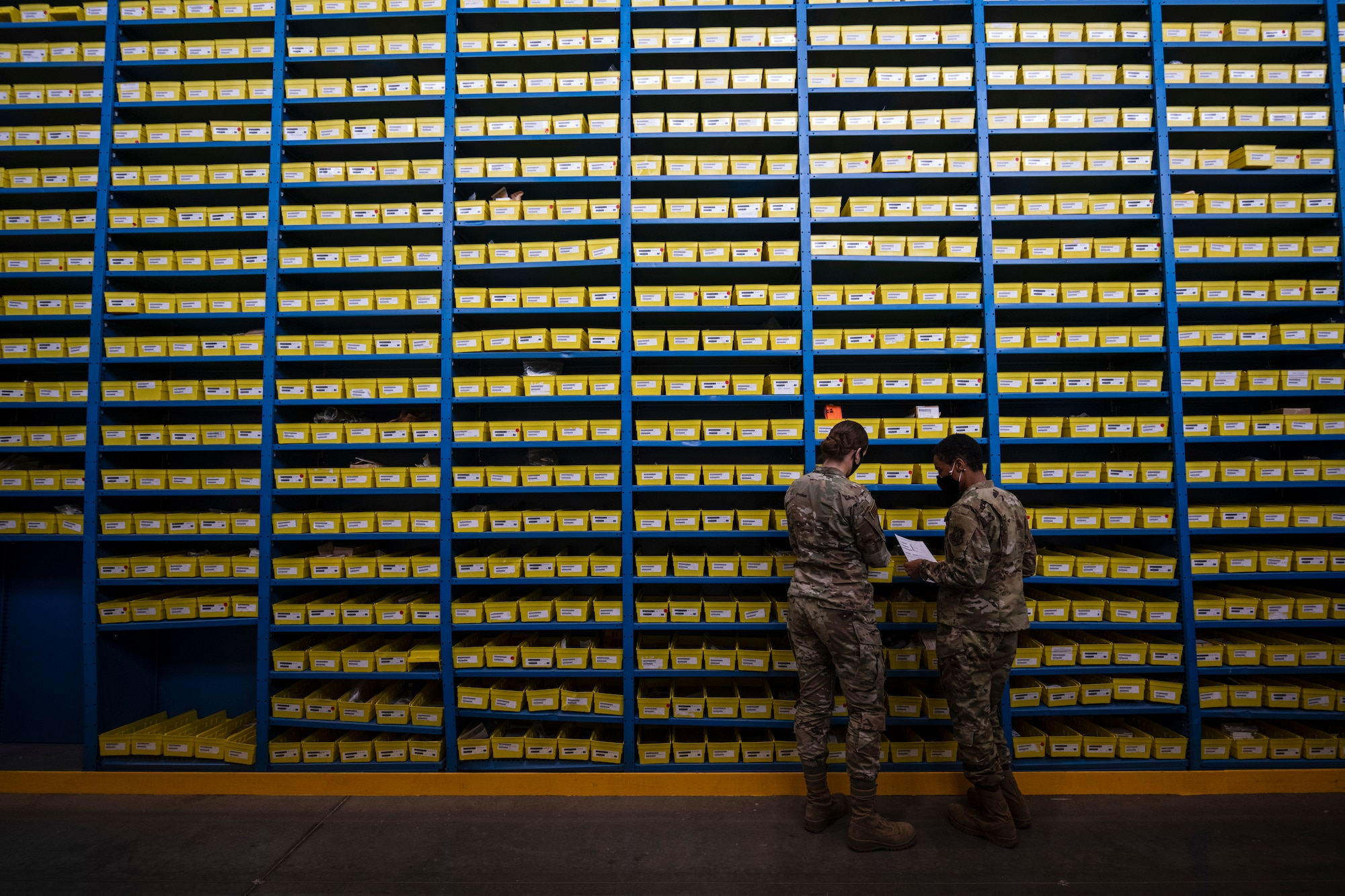 Two female Airmen stand next to each other next to a very tall wall of shelves