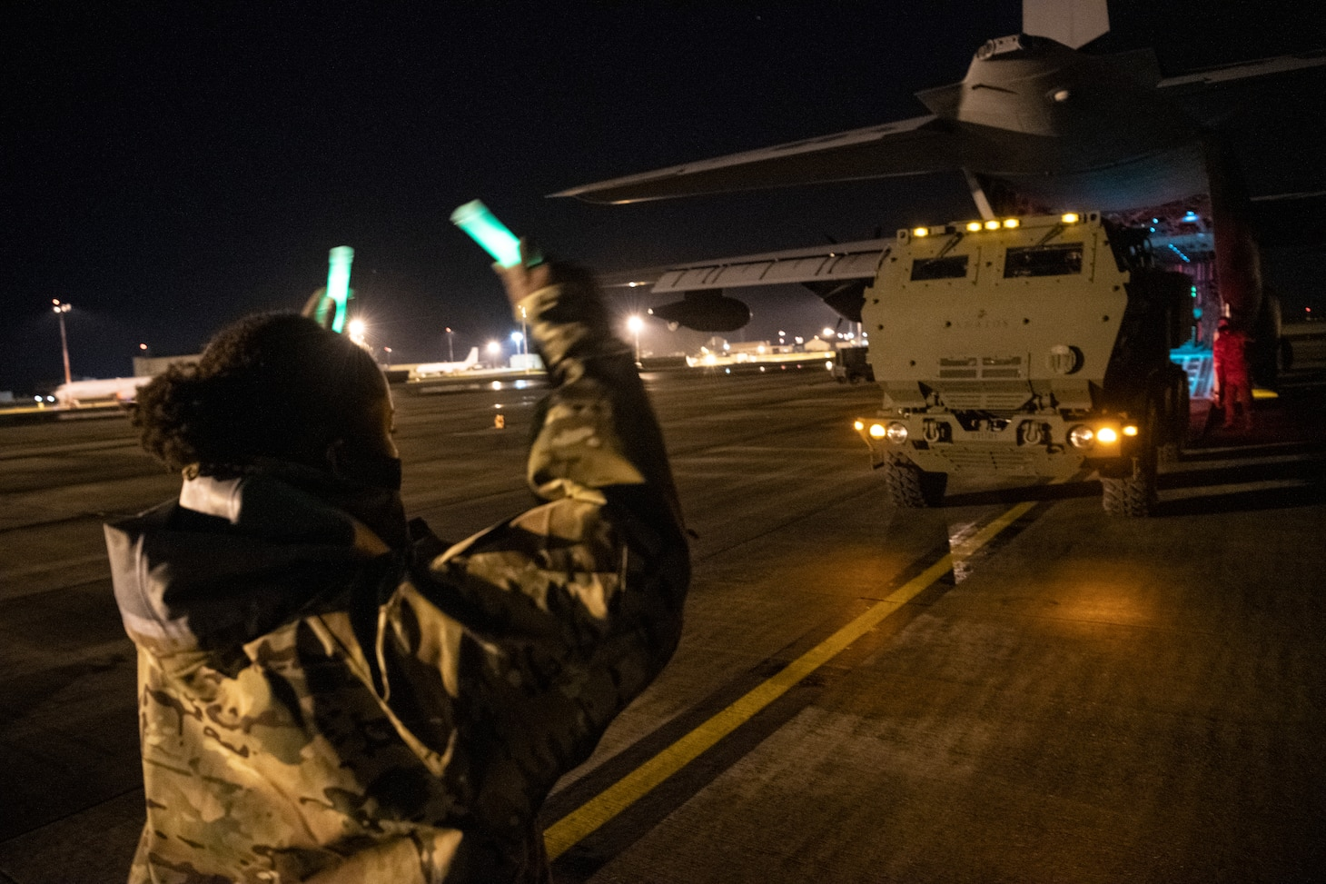 A loadmaster assigned to 352d Special Operations Wing assists marines from the 24th Marine Expeditionary Unit in off-loading a High Mobility Artillery Rocket System (HIMARS) onto an MC-130J Commando II at RAF Mildenhall on March 25, 2021 during low-visibility, night training.
