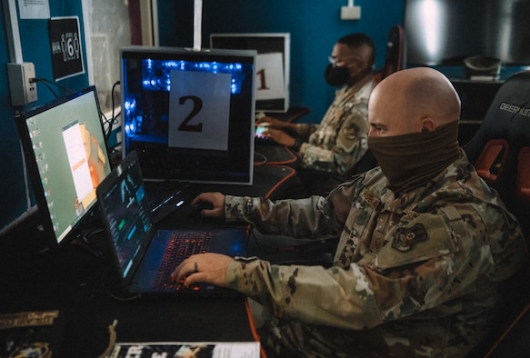 an airman sits at a laptop and plays video games