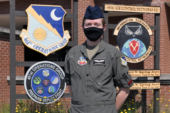 Photo show female Airmen standing in front of Group and Squadron signs outside building.