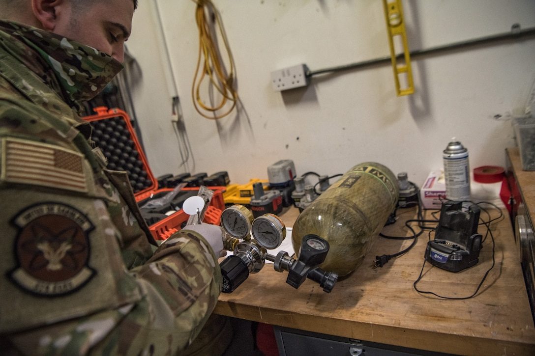 A man tests a self contained breathing apparatus on a table