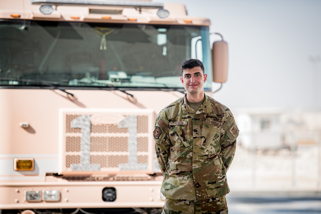 An airman poses for a photo in font of a firetruck