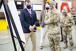 Army Maj. Gen. Darren Werner, commanding general of U.S. Army Tank-automotive and Armaments Command, center-front, receives a briefing from workers at Defense Logistics Agency Distribution Anniston, Alabama. Army Lt. Col. Ayo Oladipofapiyi, commander of DDAA, far right, accompanies him.