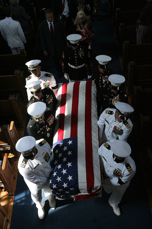 Eight pallbearers dressed in military uniforms carry a coffin draped with an American flag.