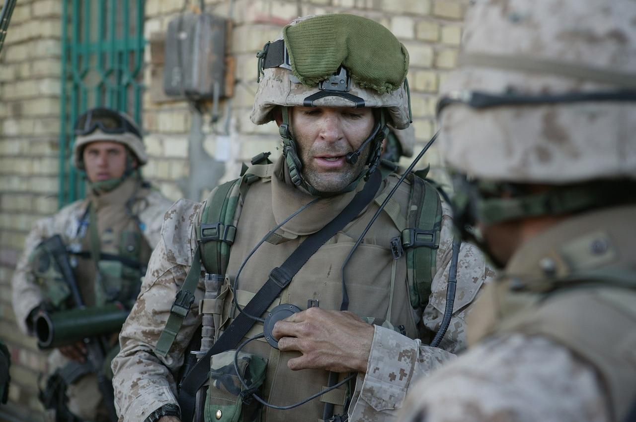 A Marine in combat gear speaks into a headset.