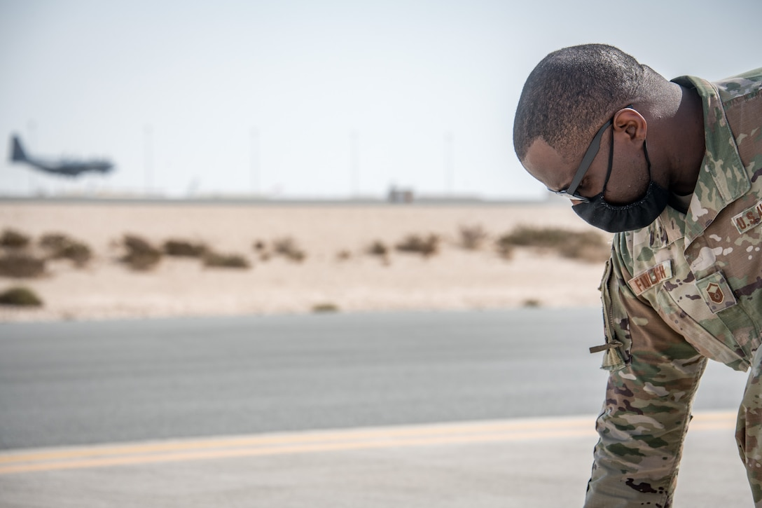 a man kneels on the flightline while a plane lands in the background