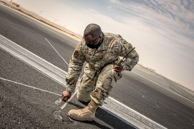 a man kneels on a flightline