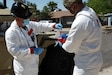 An FBI Hazardous Evidence Response Team member places the location identification tag on debris collected at a contamination point in Glendale, Ariz., April 7, during Prominent Hunt 21-1. Prominent Hunt 21-1 is part of a series of annual exercises designed to provide a realistic opportunity for an interagency team of specialists to practice and enhance their operational readiness in the event of a nuclear detonation on United States soil or abroad. (U. S. Army photo by Clem Gaines)