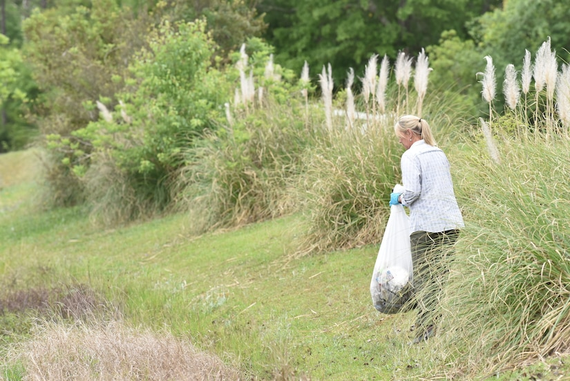 Photo shows woman picking up litter next to a lake.
