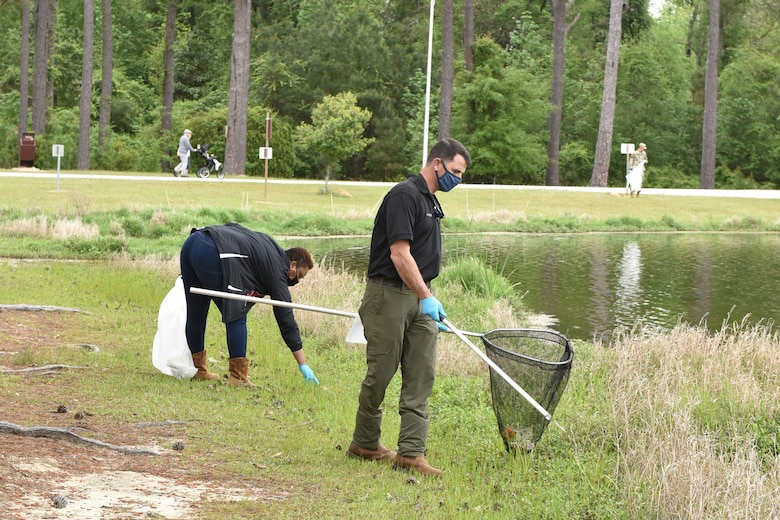Photo shows volunteers picking up litter next to a lake.