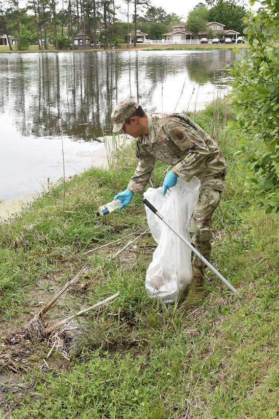 Photo shows Airman picking up litter next to lake.