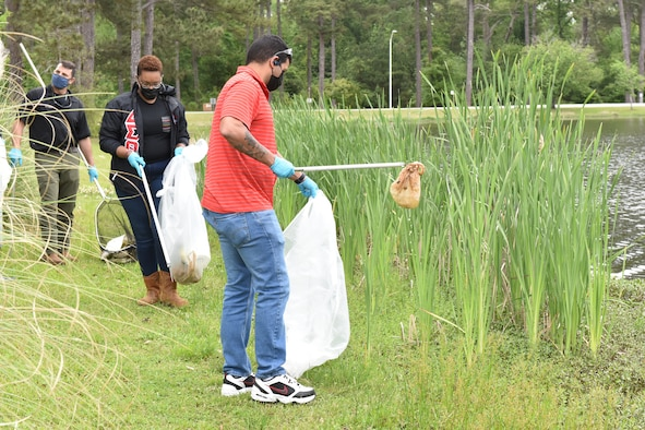 Photo shows three people pick up litter along the side of the lake.