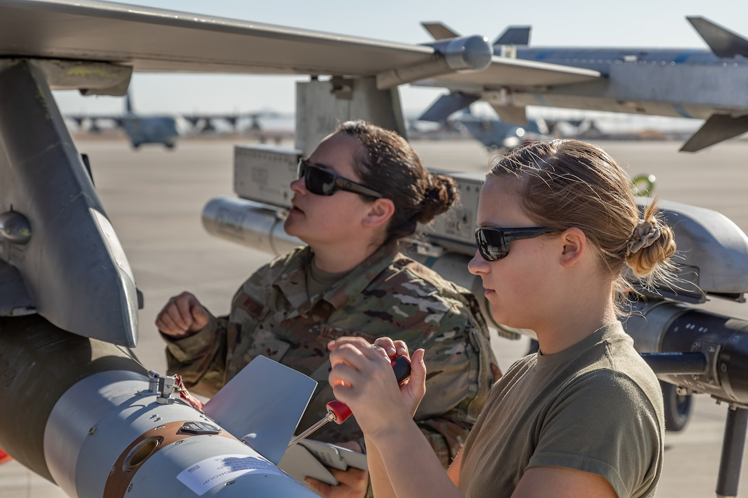 Airman First Class Madalyn Pilcher and Senior Airman Ashley Wightman, 187th Maintenance Squadron weapons loaders, load a live GBU-12 Paveway II onto an F-16C+ Fighting Falcon at Marine Corps Air Station Yuma, Ariz., April 9, 2021. The Red Tails participated in a Weapons and Tactics Instructor course capstone event March 25-April 23, 2021. The capstone was an opportunity to apply the F-16 mission set to a large-scale exercise.