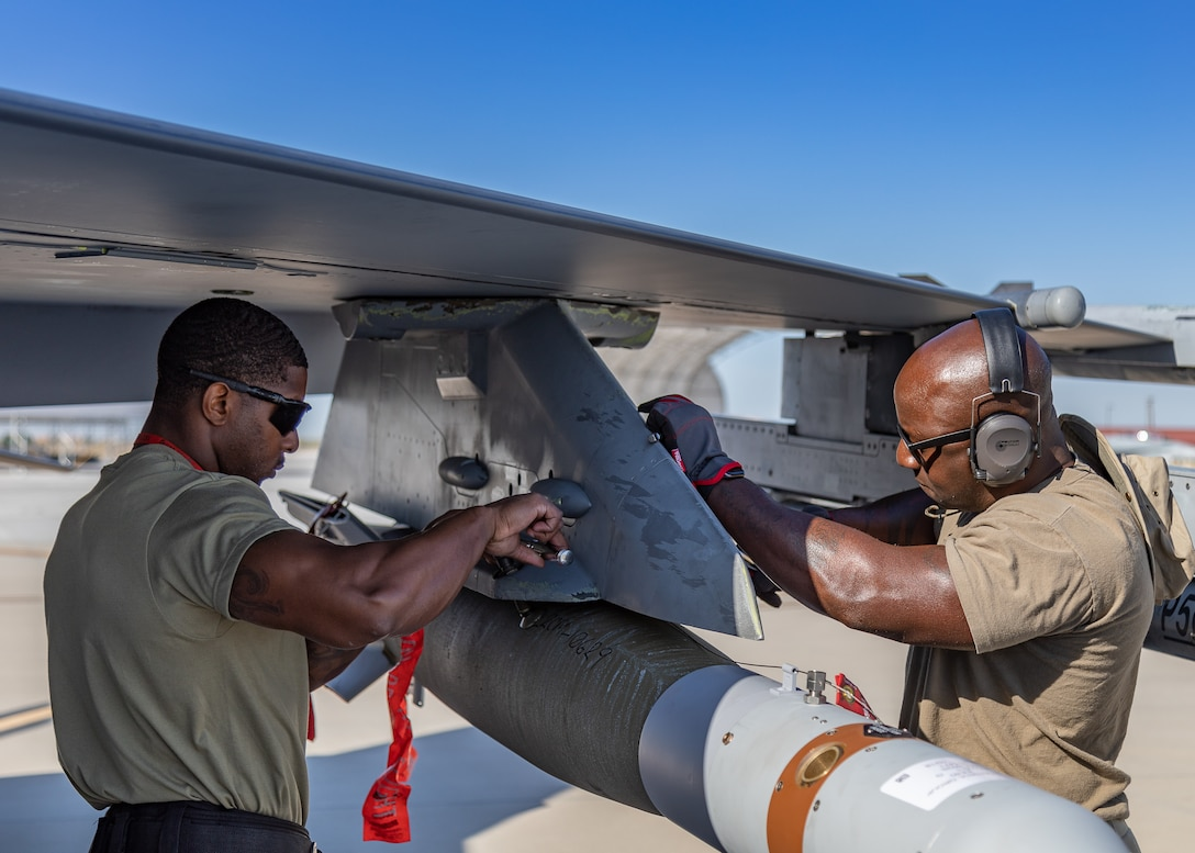 Master Sergeant Dominique Palmer and Master Sergeant Stanley Talley, 187th Maintenance Squadron weapons load crew, secure a GBU-12 Paveway II to an F-16C+ Fighting Falcon at Marine Corps Air Station Yuma, Ariz., April 9, 2021. The Red Tails participated in a Weapons and Tactics Instructor course capstone event March 25-April 23, 2021. The capstone was an opportunity to apply the F-16 mission set to a large-scale exercise.