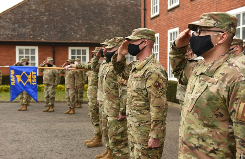 Team Mildenhall first sergeants, NCOs and senior NCOs salute during the National Anthem while conducting Retreat at Royal Air Force Mildenhall, England, April 20, 2021. The Airmen attended a first sergeant symposium to help prepare them as interim first sergeants. (U.S. Air Force photo by Karen Abeyasekere)