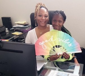 daughter sits on mothers lap in home office displaying a rainbow fan with good vibes written on it