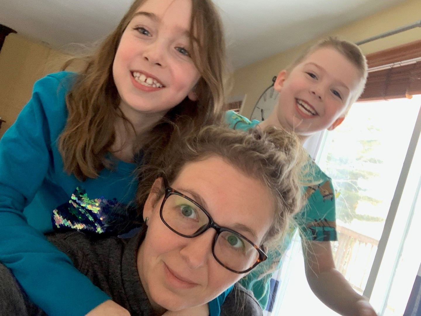 Mom with two kids hanging off her