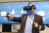 IMAGE: Naval Surface Warfare Center Dahlgren Division (NSWCDD) Technical Director John Fiore interacts with a concept captured in virtual reality that would enable the collection, curation, collaboration and conduction of Next Generation Combat Information Center (CIC) data and missions. Fiore engaged in the immersive experience made possible by the Next Generation CIC Tactical Advancements for the Next Generation Project developed by Johns Hopkins Applied Physics Lab scientists and sponsored by the Missile Defense Agency to create engagement and awareness around CIC possibilities through speculative design, looking ahead to 20 years in the future.