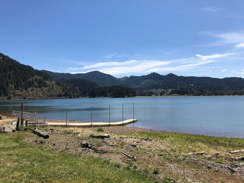A pier at a lake of water, with hills and a blue sky in the background.
