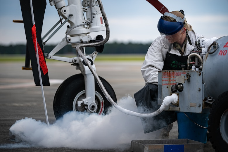 A photo of an Airman observing liquid oxygen as it vents from an aircraft