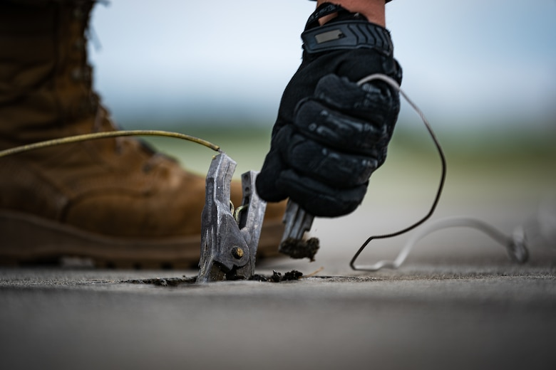 A photo of an Airman removing a grounding clamp