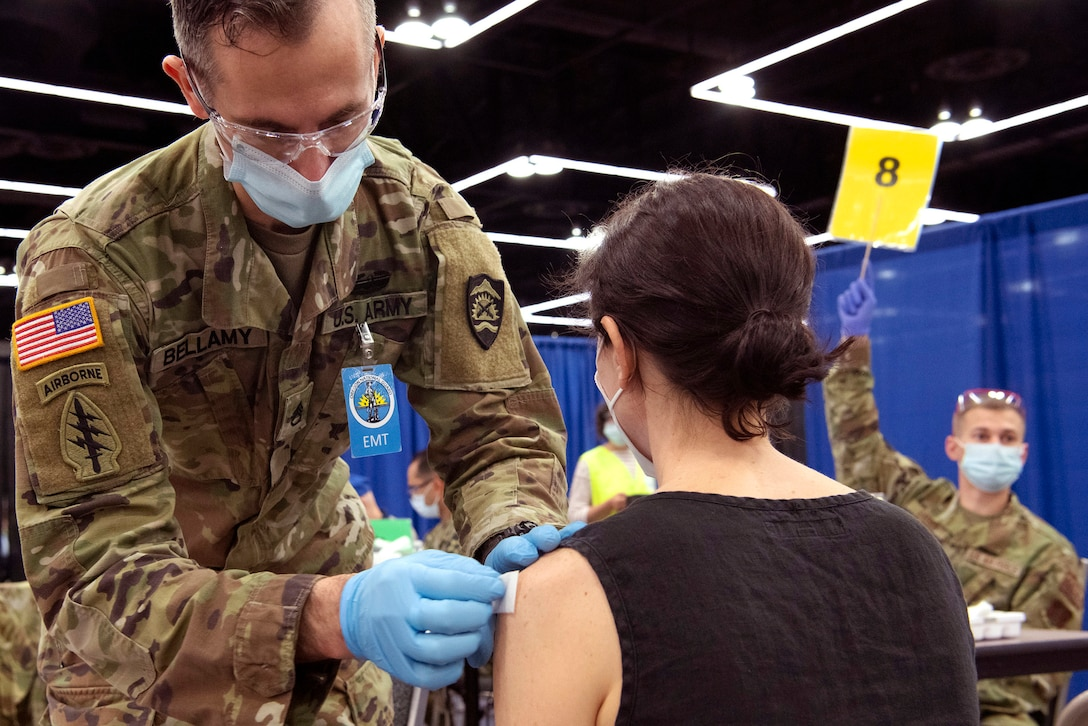 A soldier wearing a face mask and gloves gives a vaccine to a resident.