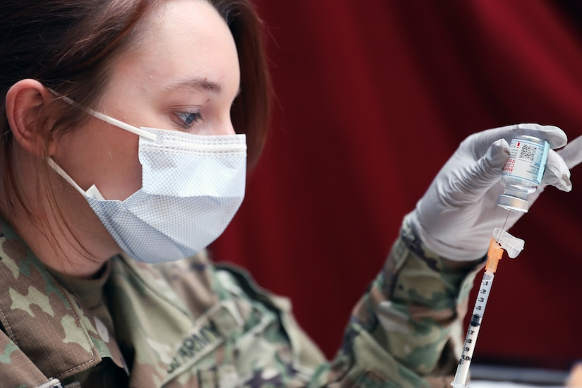 A soldier wearing a face mask and gloves holds a vial while inserting a syringe into it.