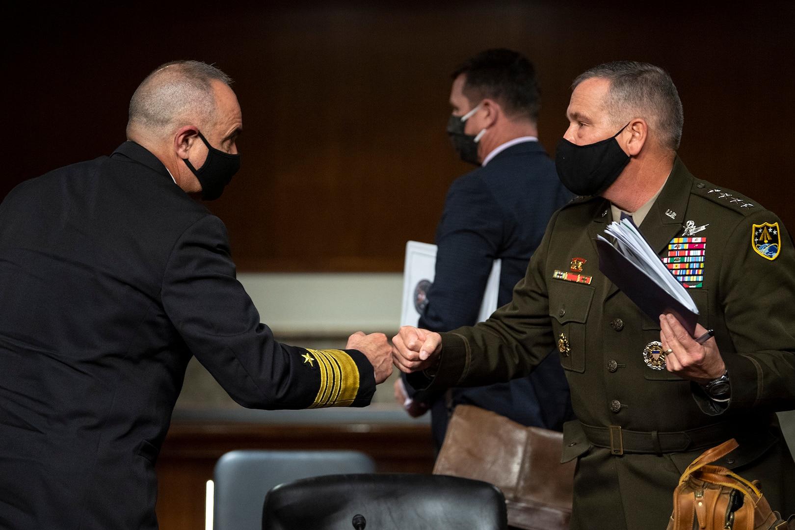 Military officers fist bump following SASC hearing.