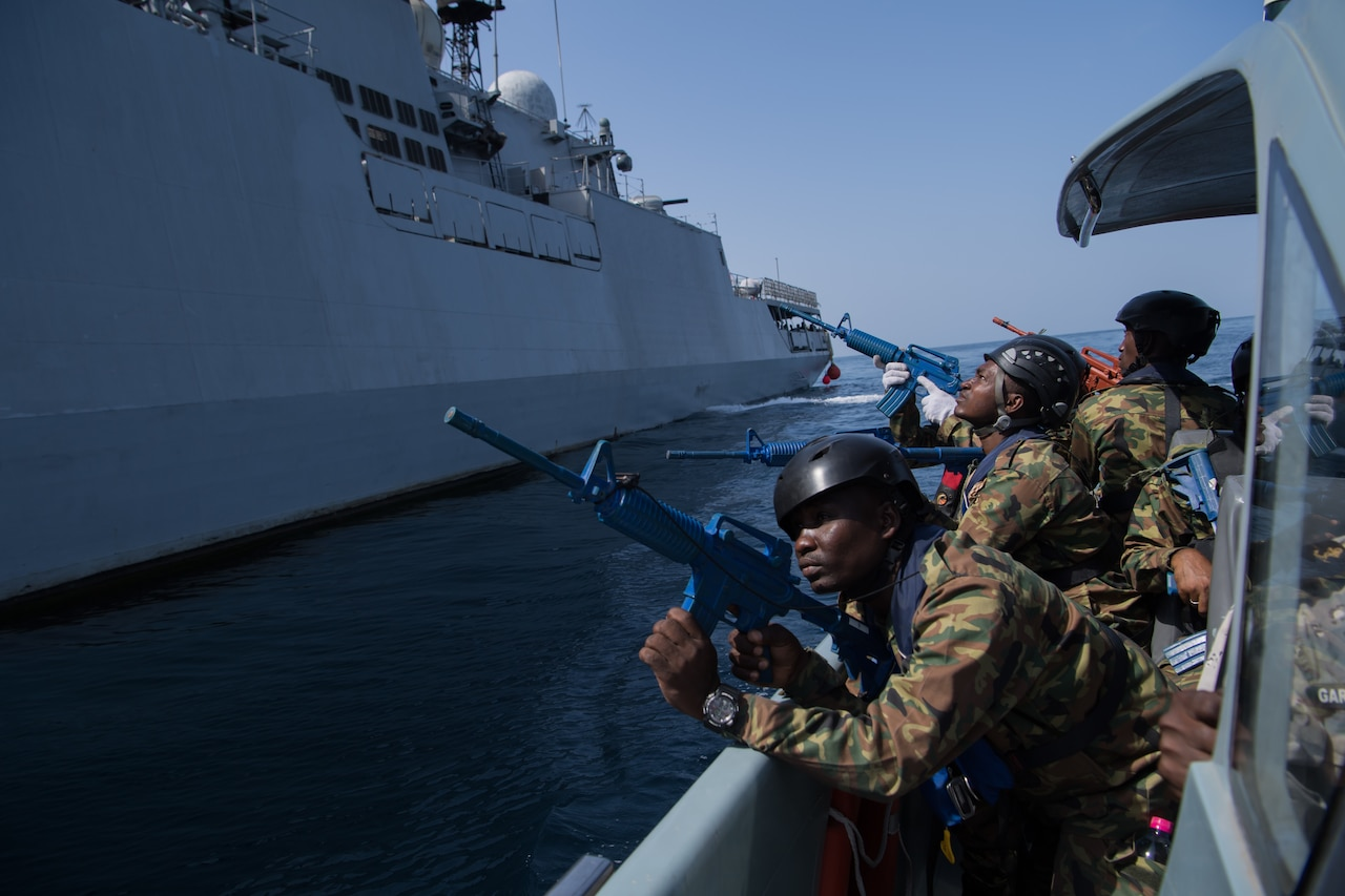 From the deck of a ship, service members point guns upward at a large ship.