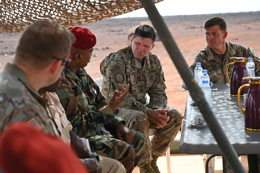 Shaded by an umbrella, five men in military uniforms sit at a table outside and talk; a desert landscape is in the background.