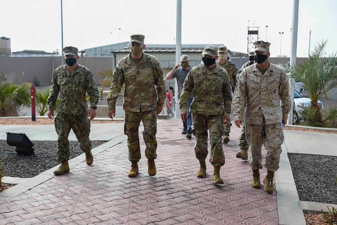Four men in military uniforms walk into a building.