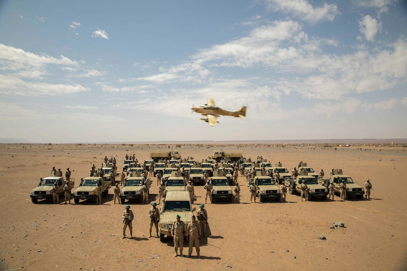 An aircraft flies over foreign military vehicles and service members in the desert.