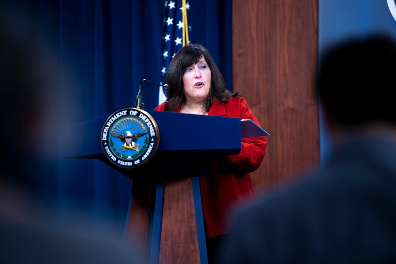 A woman stands at a lectern.