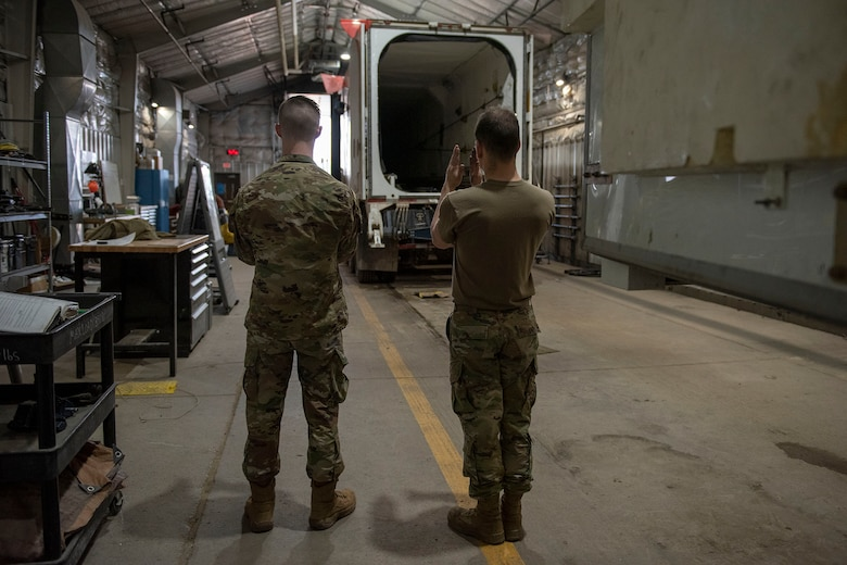 The team chief guides a transporter erector inside the hanger for the start of the missile roll transfer.