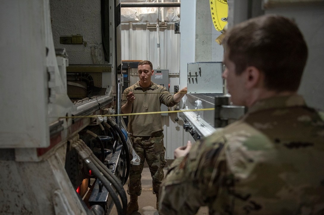 Two Airmen measure the distance with tape measures two transporter vehicles before the start of a missile roll transfer.
