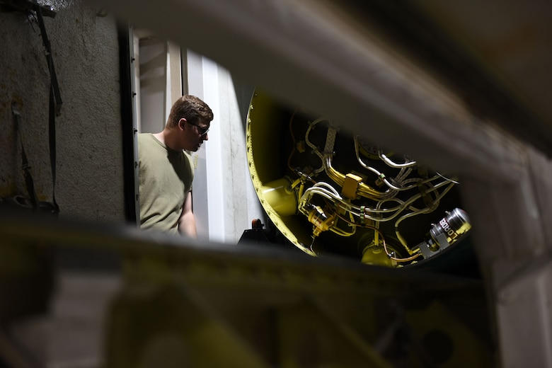 Airman peers inside of the T.E. van to inspect the booster of the missile.