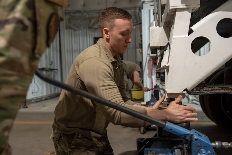 Airman levels the rear of the transporter erector so the missile can be transported from one vehicle to another without incurring damage.