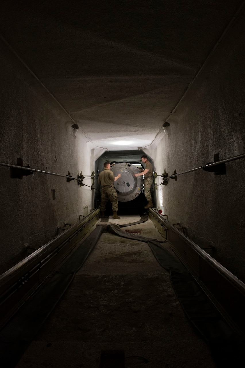 People in a tunnel secure a missile.