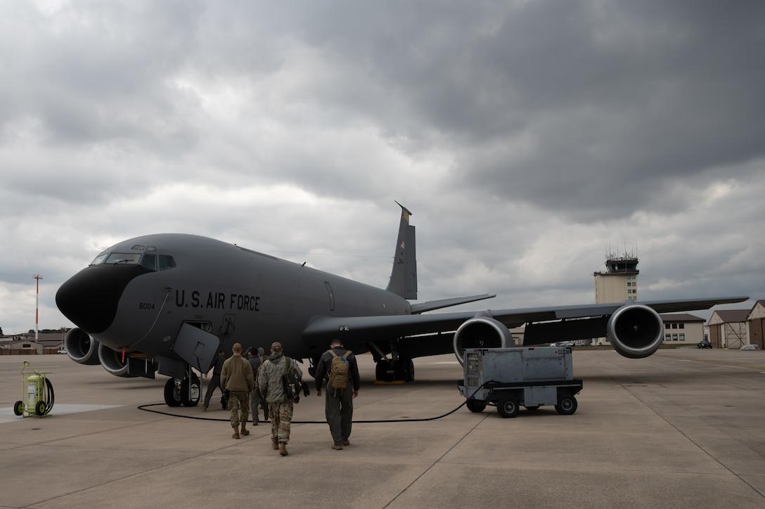 Airmen walking toward an aircraft.