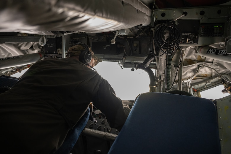 Airman laying over a control panel on an aircraft.
