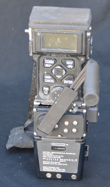 A removable hand-crank provides on-the-go power to the Surge charging device, shown here with the Combat Survivor Evader Locator radio (top) and battery (bottom) all connected. (Photo courtesy of Combat Power Solutions, LLC)