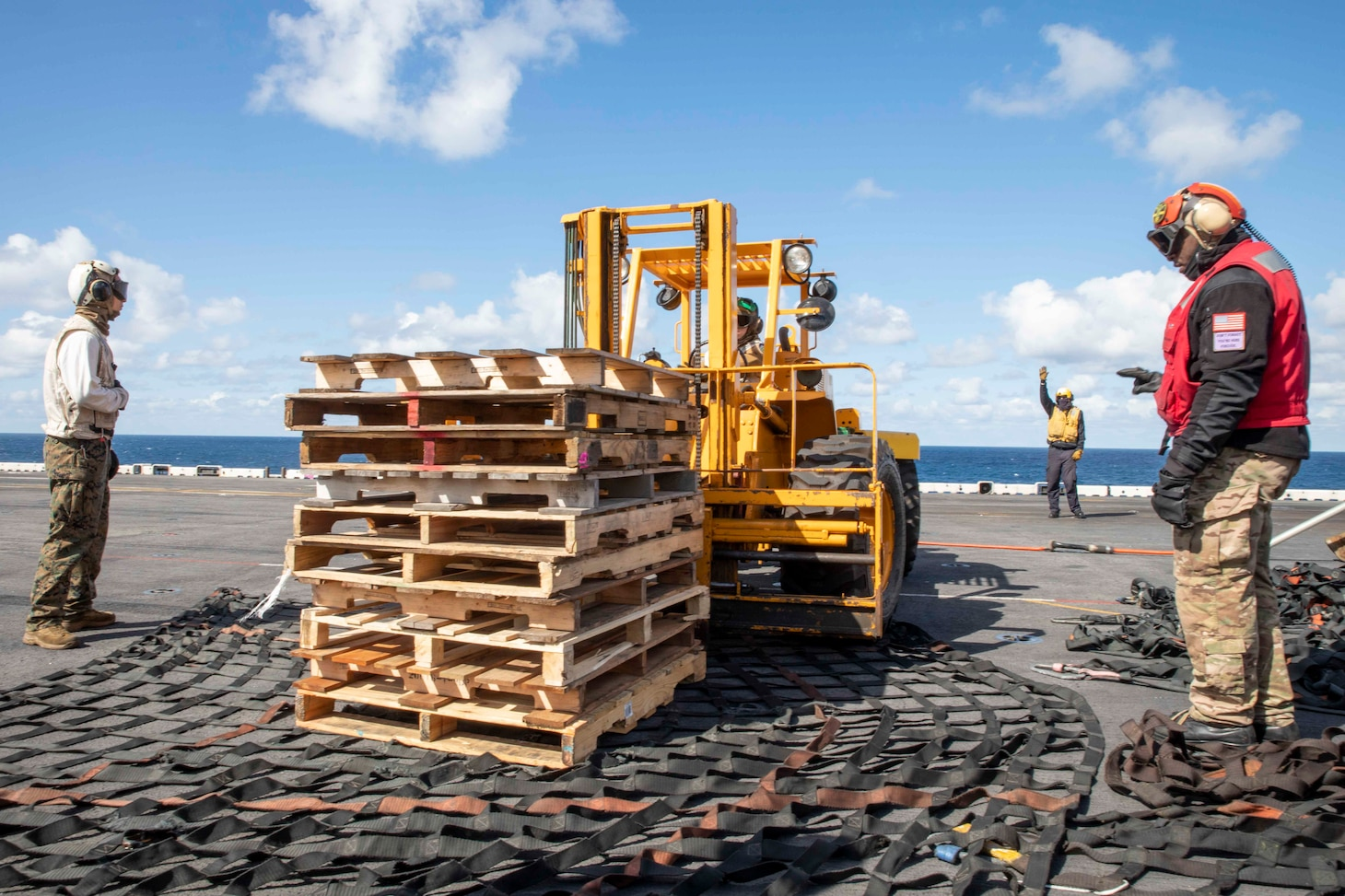Sailors assigned to the Wasp-class amphibious assault ship USS Iwo Jima (LHD 7) and Marines from the 24th Marine Expeditionary Unit (24th MEU) prepare a pallet stack for offload during a replenishment-at-sea, April 11, 2021.