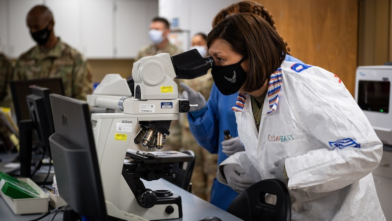Chief Master Sergeant of the Air Force JoAnne S. Bass, looks through a microscope during a tour of Barksdale Air Force Base, Louisiana, April 21, 2021.