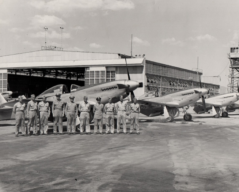 10 Airmen stand next to each other on a flight line in front of three planes and a hangar