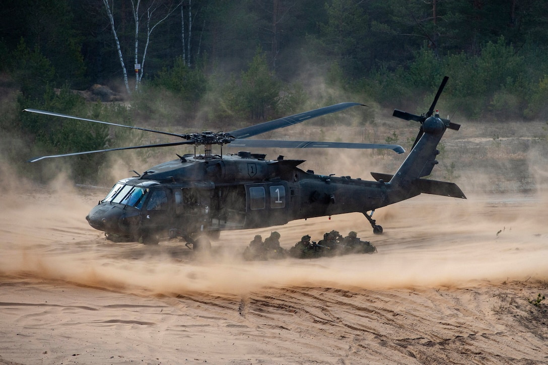 Soldiers aim weapons near a helicopter surrounded by clouds of dust.
